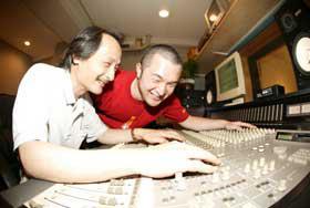 スタジオ録音調整室で音楽製作に取り組む村上氏とスタッフの五十嵐氏